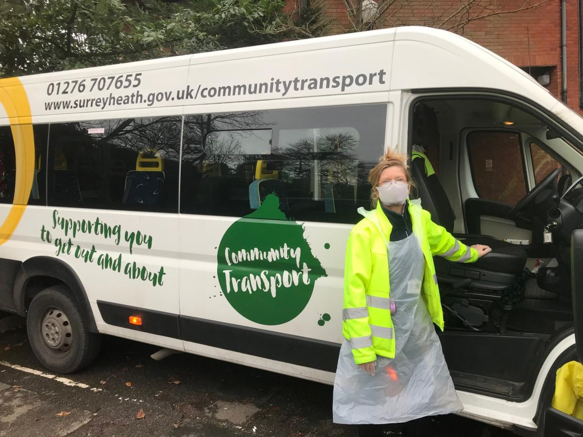 One of the Community Services team wearing a mask stood next to a Community Transport buses